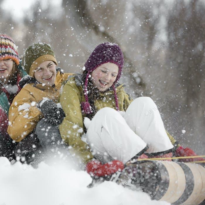 Drei Kinder sitzen auf einem Schlitten, der einen Schneehang hinunterrutscht.