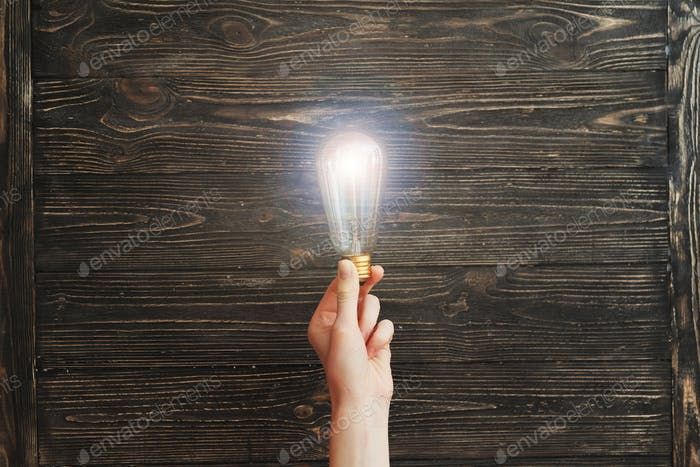 Hand holding light bulb on wooden board