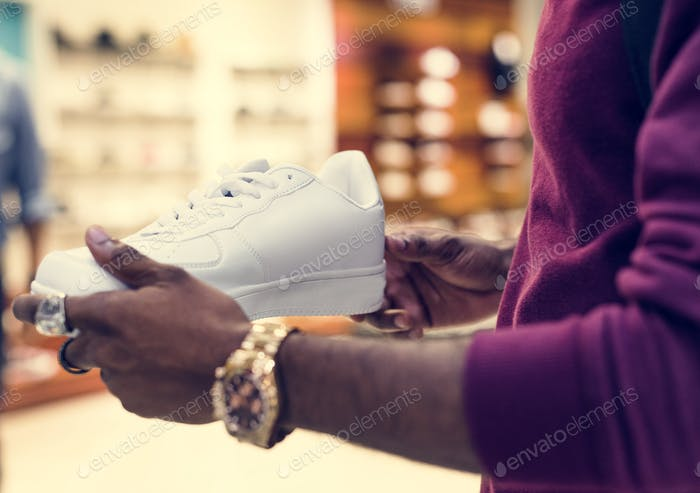African man holding a white sneakers