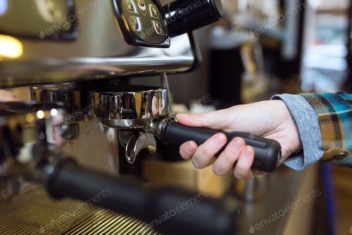 Waitress making coffee using a professional machine in a coffee