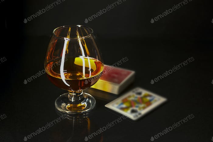 Cognac glass and playing cards
