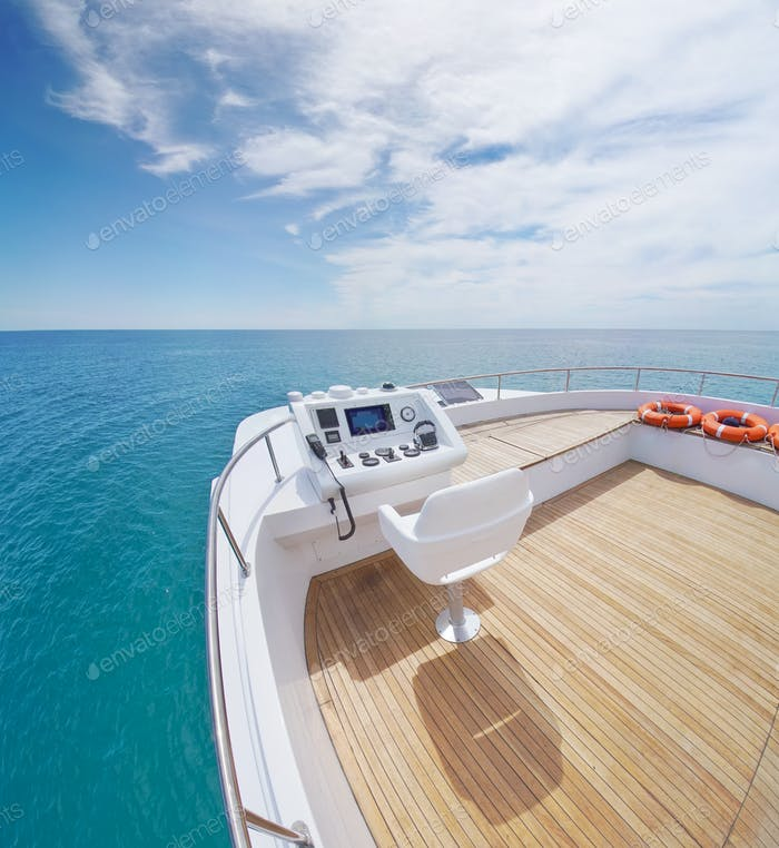 View from yacht flybridge open deck on the calm sea water at day.