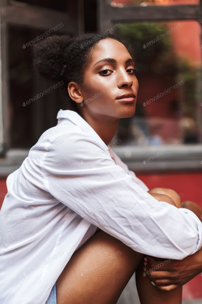 Portrait of thoughtful african girl with dark curly hair in whit