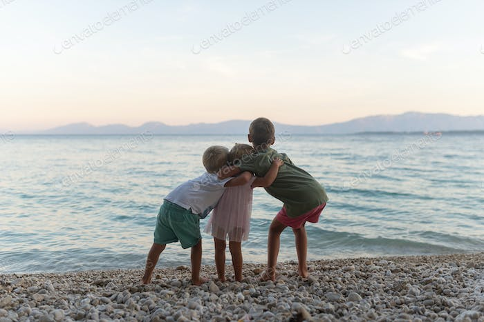 Three sibling hugging on the beach