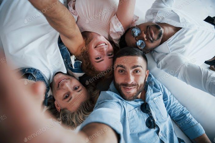 Junge Leute legen sich hin und machen ein Selfie