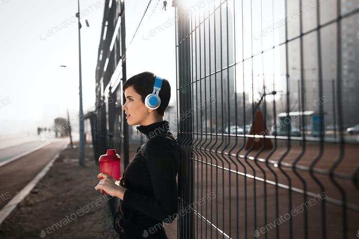 Woman listening to music while working out and jogging outdoor