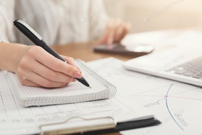 Closeup of woman hand writing notes and using calculator