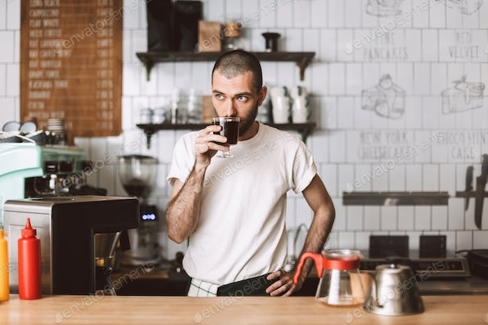 Young barista at bar counter smelling filter coffee dreamily looking aside in cafe