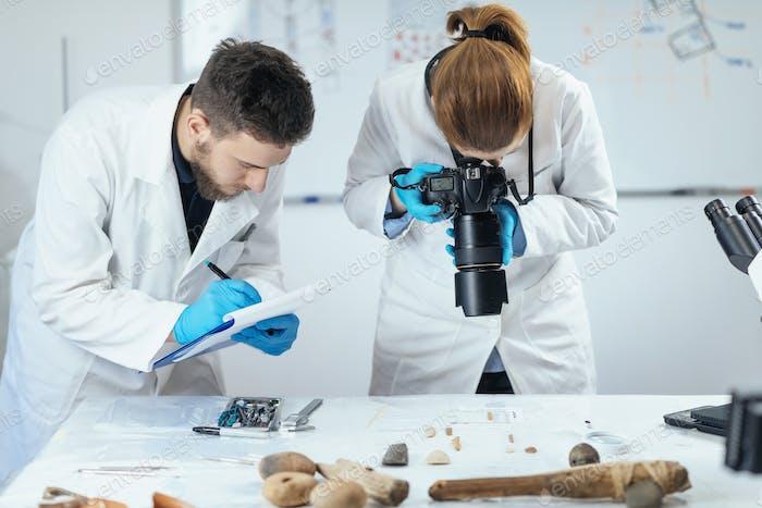 Archäologieforscher im Labor, Dokumentieren von Artefakten mit Kamera