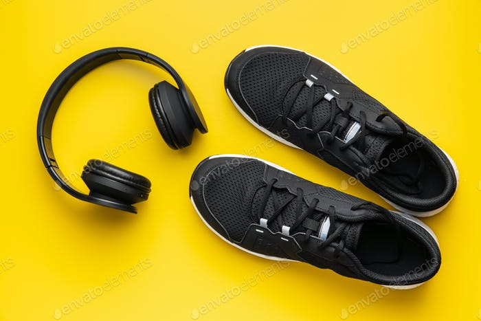 Fitness concept. Black sports shoes and headphones
