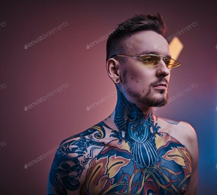 Eingefärbtes männliches Modell posiert in einem Neonstudio mit halbnacktem tätowierten Körper und Sonnenbrille.