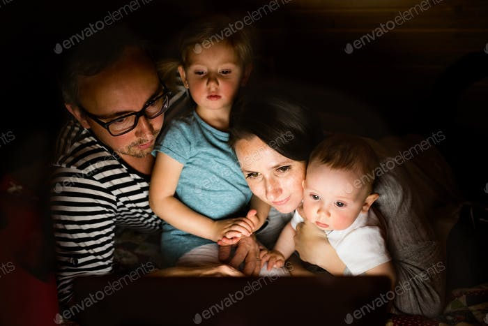 Young parents with little children and laptop at night.
