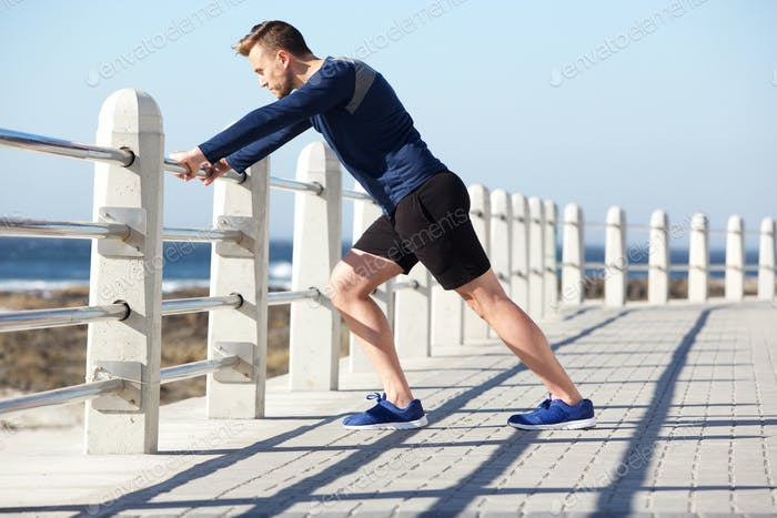 healthy young man stretching outside for exercise
