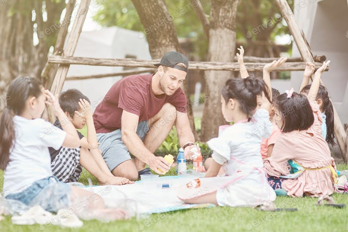 Pleasant man conducting a lesson for thai children outdoors