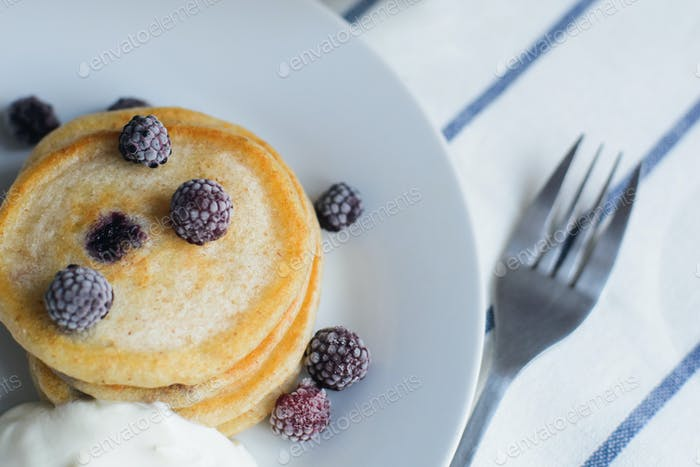 fritter or pancakes with black raspberry with sour cream on dish