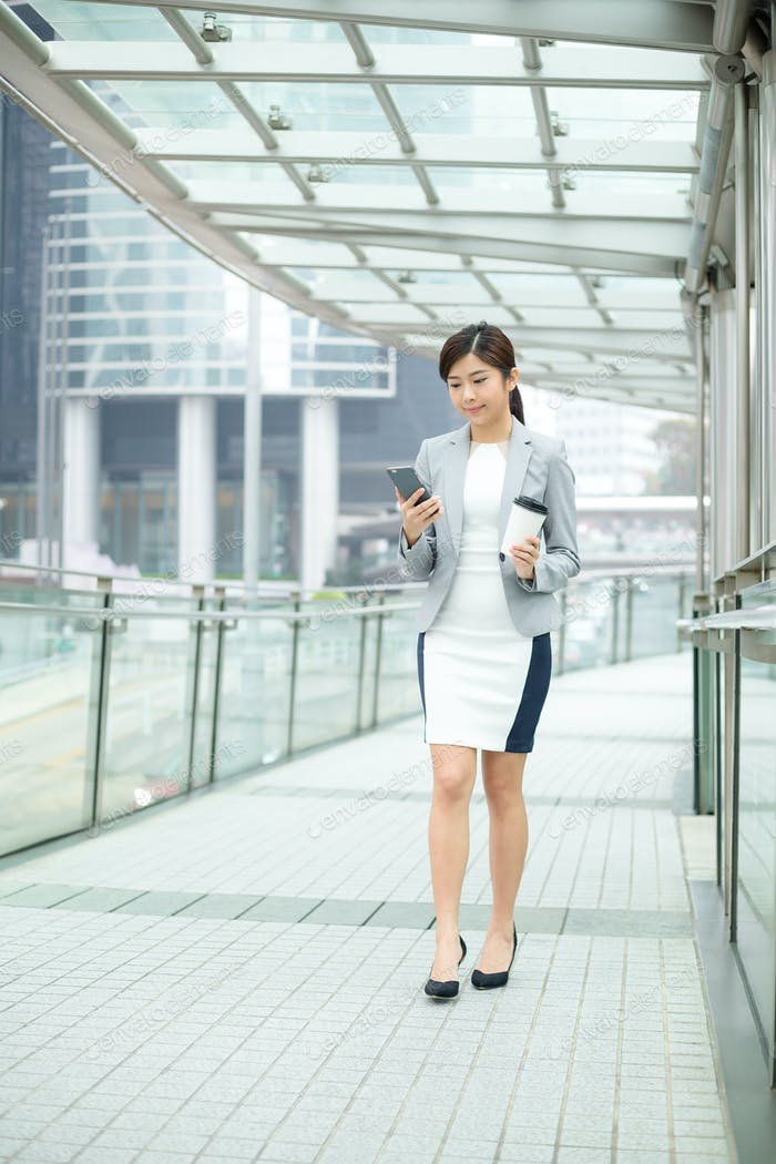 Businesswoman using mobile phone to send a message