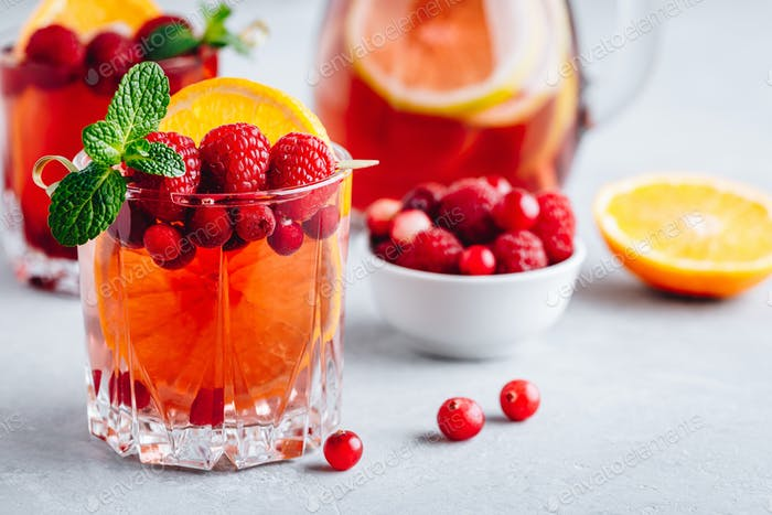 Raspberry Cranberry Sangria Punch or Mojito in glass with orange slices and mint