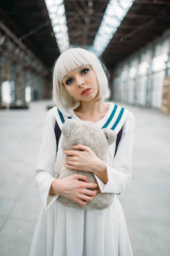 Anime style blonde girl hugs teddy bear