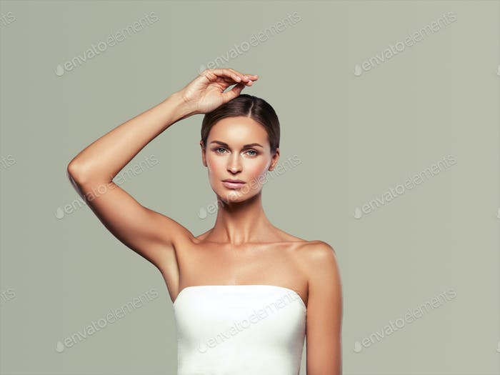 Woman beauty face healthy skin natural makeup beautiful young model with hands. On gray.