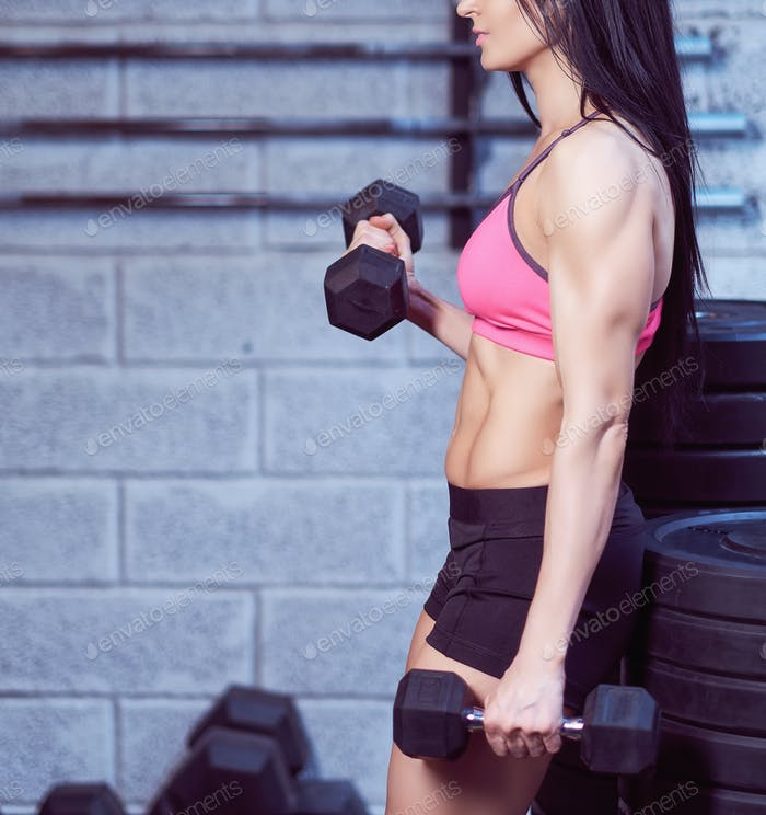 Strong brunette sporty woman in a sportswear doing exercise with dumbbells at a gym.
