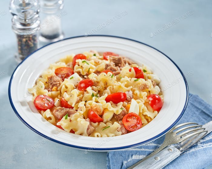 Healthy Fusilli or rotini pasta salad with tuna, vine tomatoes and mozzarella cheese.