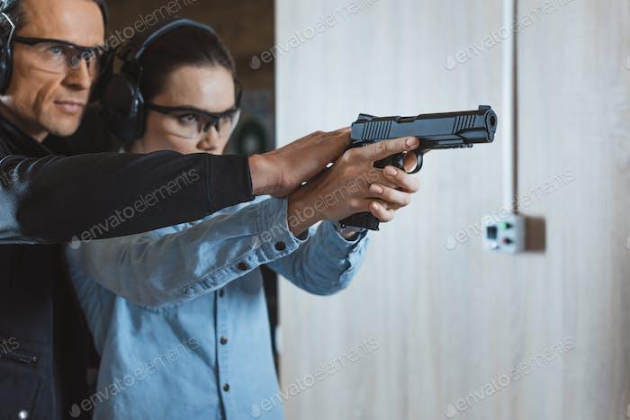 instructor masculino ayudando al cliente a disparar con arma en el campo de tiro