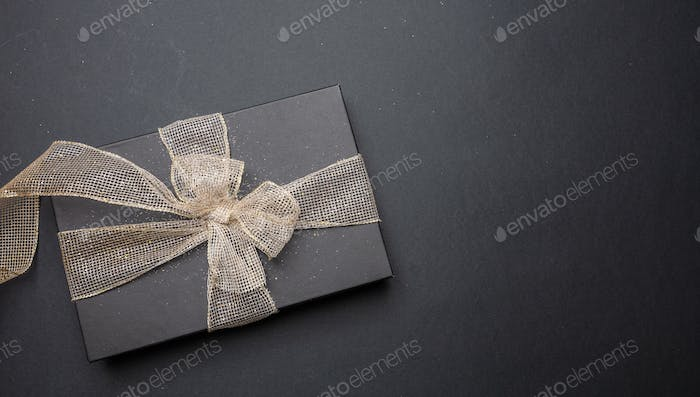 Black gift box with shiny ribbon on black background, top view