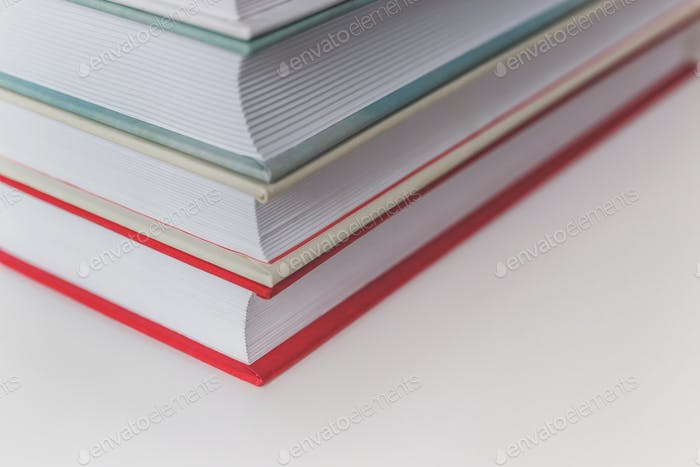 Book stack on white table. Close-up view