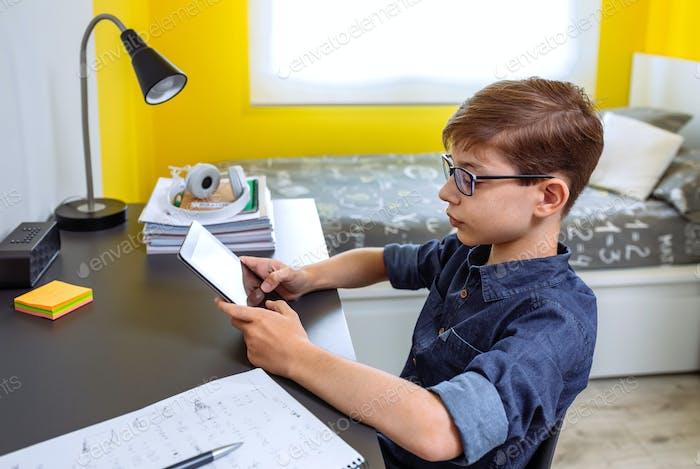 Preadolescente haciendo los deberes con una tableta