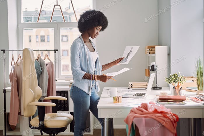 Beautiful young African woman analyzing fashion design sketches