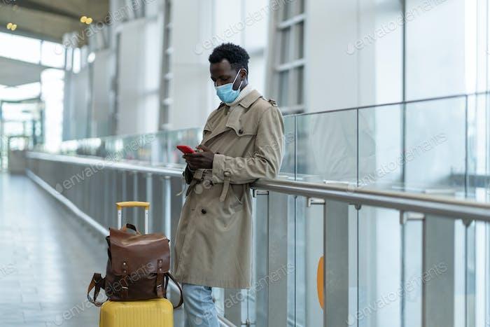 Schwarzer Mann steht am Flughafen, trägt eine Gesichtsmaske, um sich vor Grippe, Coronavirus und Covid-19 zu schützen