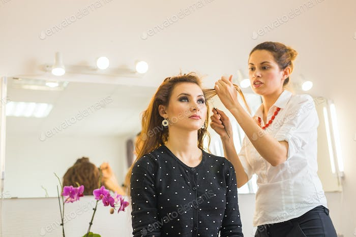 beauty and people concept - happy young woman with hairdresser at hair salon.