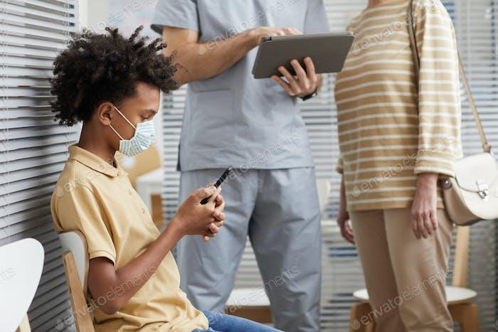 Boy Wearing Mask in Hospital Line