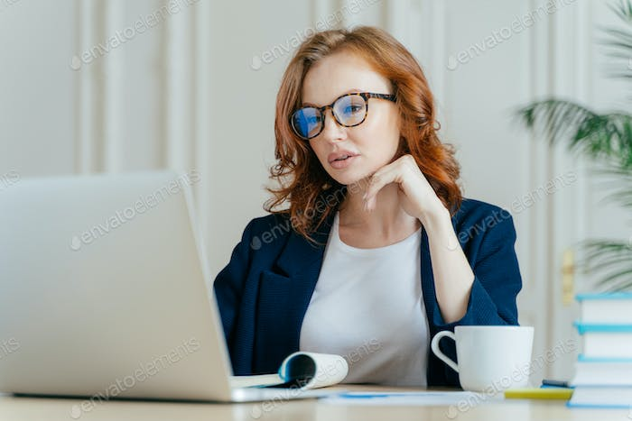 Atttactive businesswoman concentrated in monitor of laptop computer, has serious focused gaze