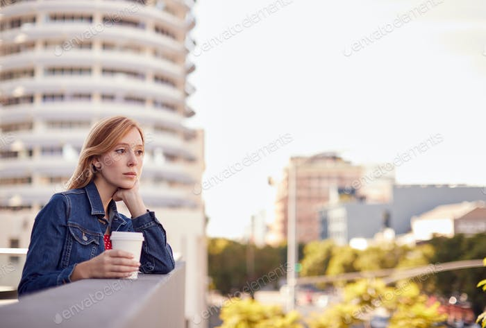 Portrait Of Thoughtful Businesswoman Standing Outside Office Building With City Skyline Behind