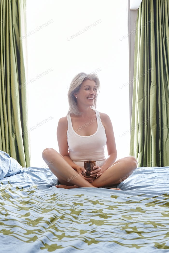 Attractive vivacious mature Caucasian woman sitting on her bed cross legged smiling