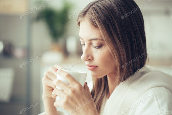 Girl with white cup in hands. Casual woman portrait with drink tea or coffe female indors home