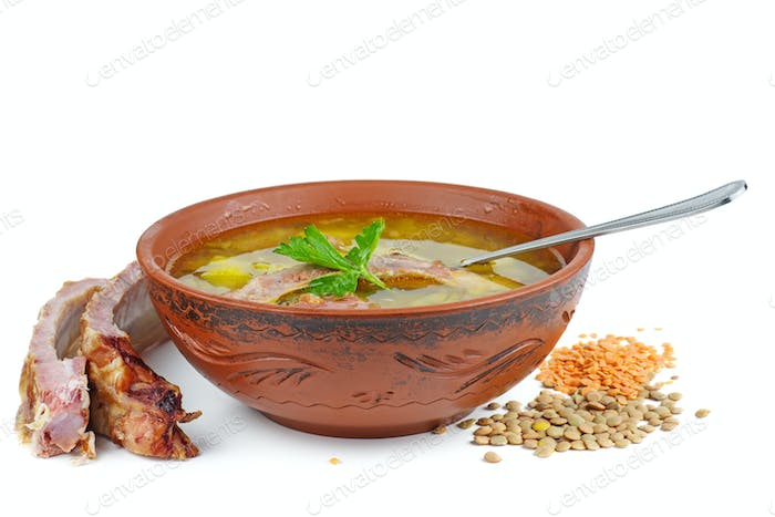 Clay bowl with lentil soup and smoked pork ribs isolated on white background.