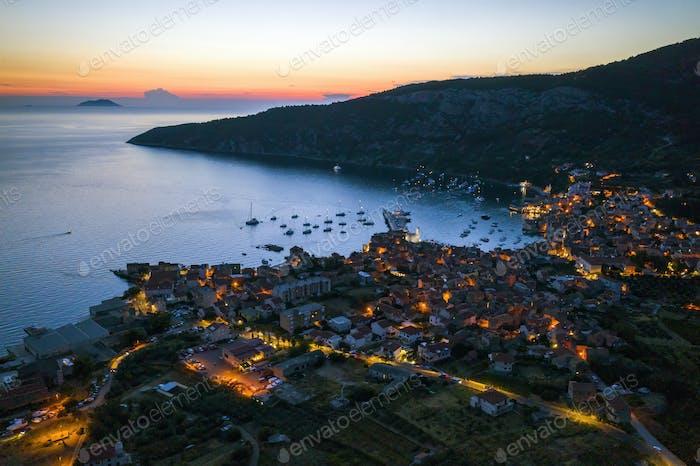 Nocturnal aerial view of seaside town of Komiza in Croatia at night