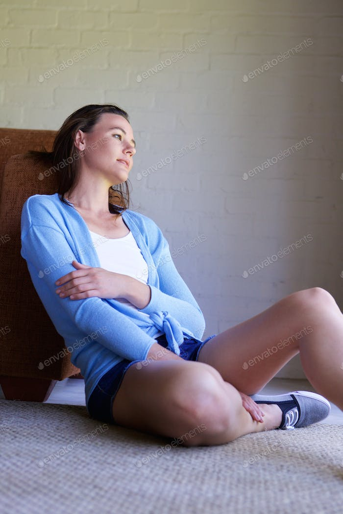 Pensive young woman sitting on floor at home