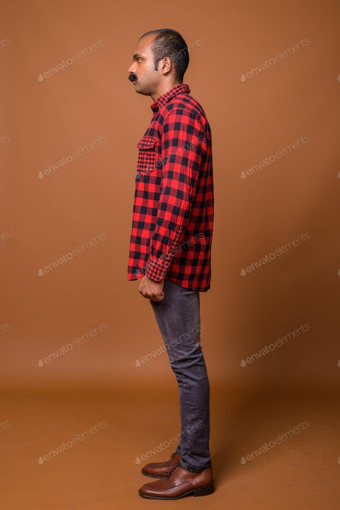 Full body shot profile view of Indian hipster man with mustache