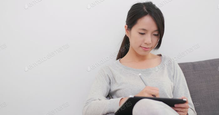 Woman drawing on tablet computer at home