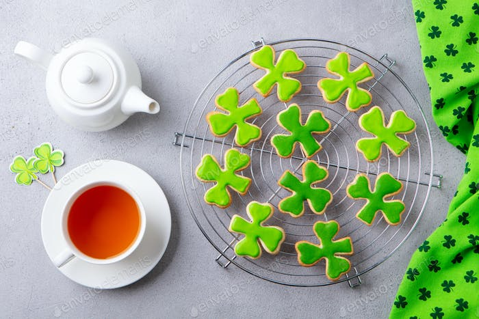 Shamrock cookies on cooling rack with cup of tea, St. Patrick's Day dessert. Grey background