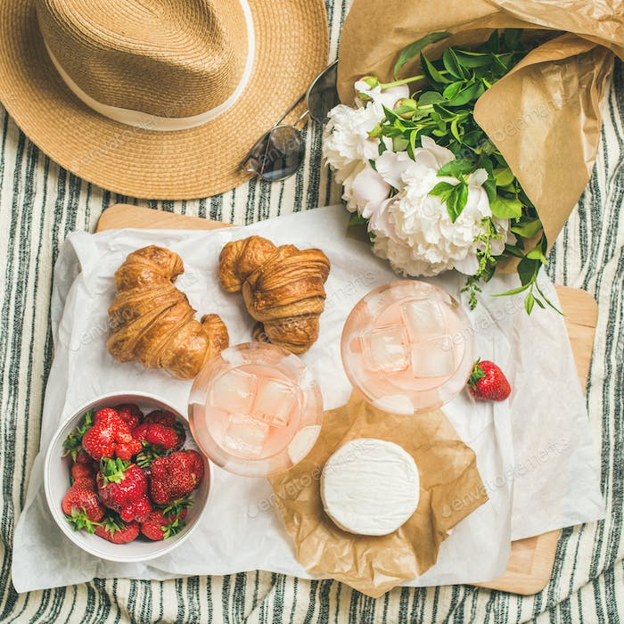 Flat-lay of rose wine, strawberries, croissants, brie cheese, square crop