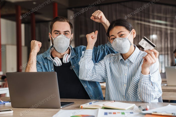 Photo of multinational students in medical masks making winner gesture