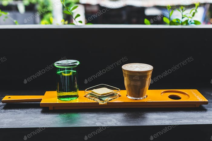 Unusual serving coffee in a cafe: cappuccino, water and biscuit on yellow wooden stand