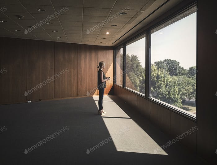 Woman Standing in Empty Office Room at Window