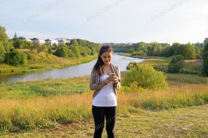 Young beautiful Asian woman using phone against relaxing view of nature