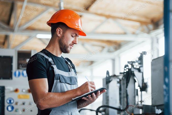 Mit Notizblock in den Händen. Industriearbeiter in Innenräumen in der Fabrik. Junger Techniker mit orangefarbenem hartem Hut