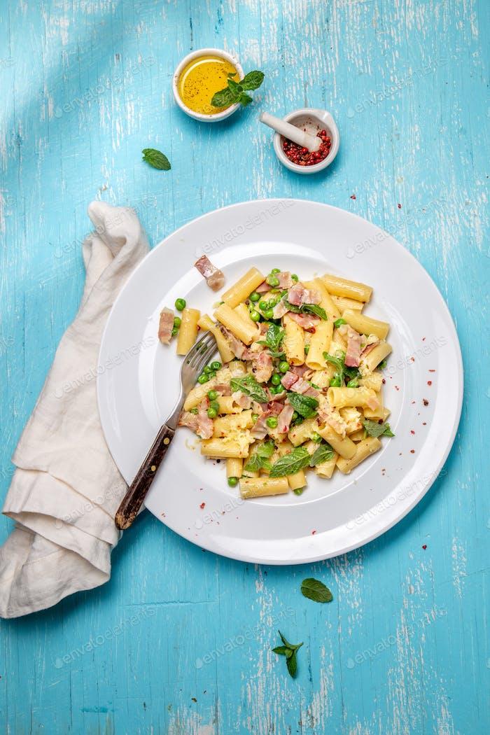 Italienisches Rezept Pasta Tortilloni mit grüner Erbse, Minze, Käse, geräuchertem Speck und Käse. Oben